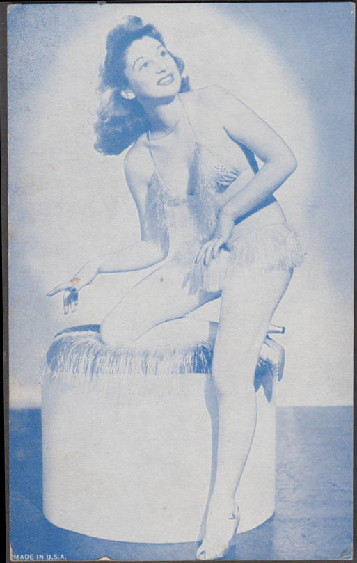 Brunette in 2-piece suit kneels on ottoman pin-up arcade card 1940s