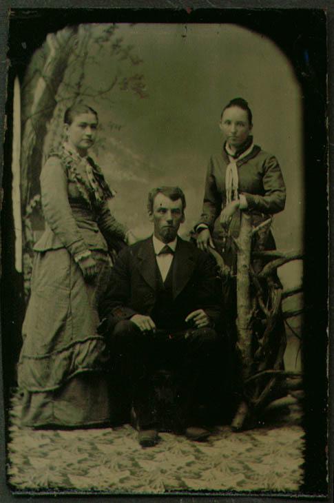 2 standing women 1 seated man 1 goatee rustic tintype