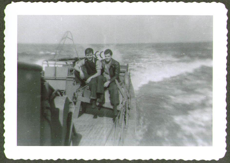 2 crewmen sit on depth charges USCG CG-83465 photo 1944