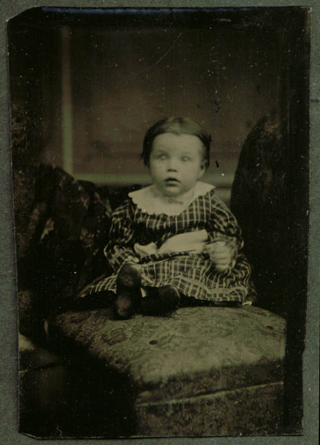 Surprised seated baby in plaid stuffed chair tintype