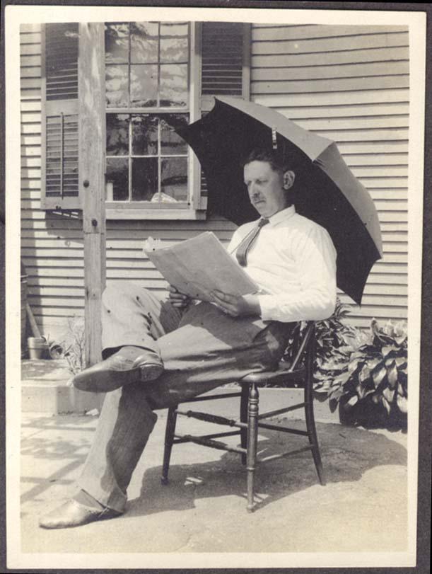 Joseph Frankland reads under umbrella photo 1930s