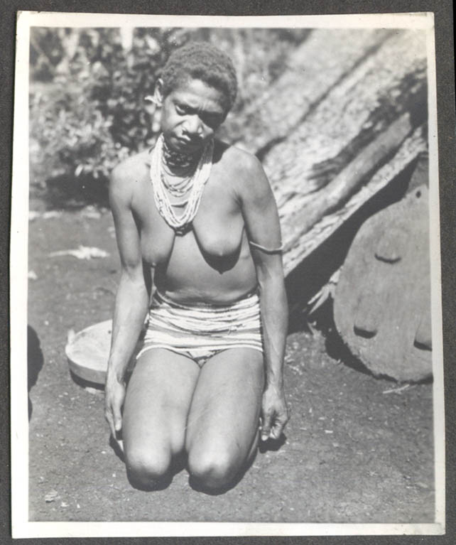 Scowling topless African woman kneeling photo 1930s