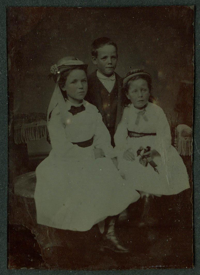 2 girls & a boy studio tintype ca 1860s fancy whote dresses, straw hats flowers
