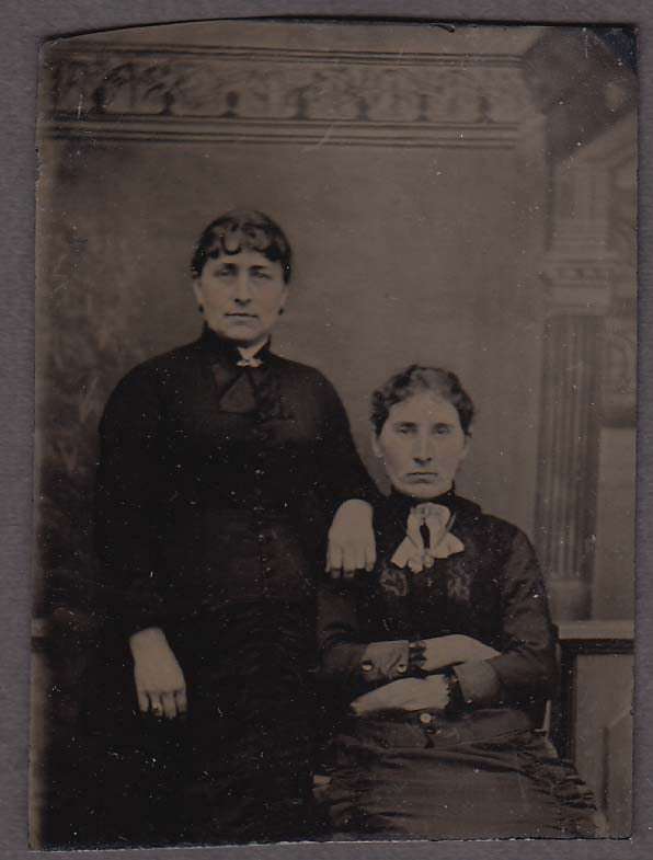 2 middle-aged women 1 seated arms folded pinked cheeks tintype 1860s