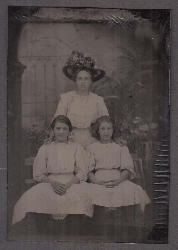 2 seated girls white dresses standing woman flowered hat studio tintype 1860s