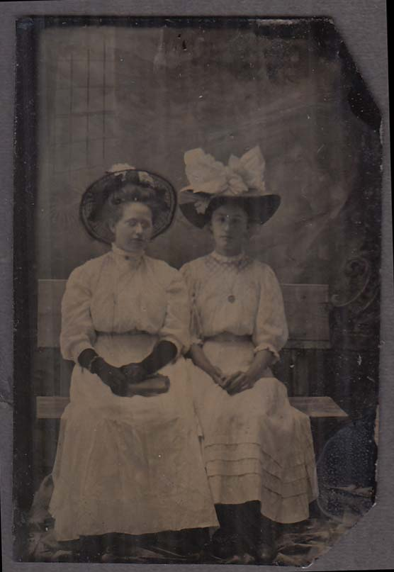 2 seated women in fancy straw hats 1 with gloves & purse studio tintype 1860s