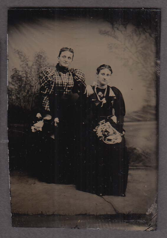 2 middle-aged women in puffy-sleeve dresses studio tintype 1860s