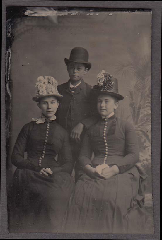 2 seated women fancy hats standing man tall derby studio tintype 1860s