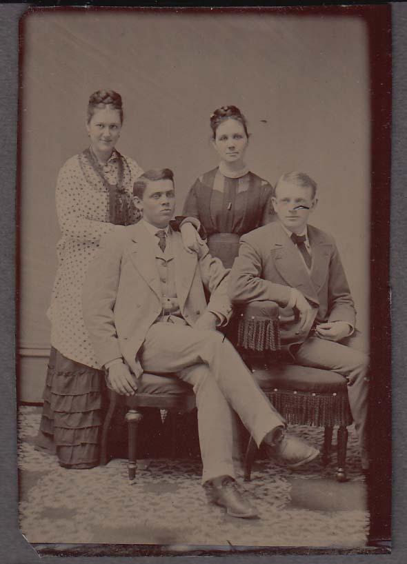 2 couples - women hair braided on top; men in grey suits studio tintype 1860s