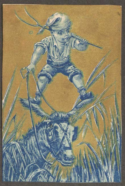 Boy with pitchfork stands on donkey ears trade card