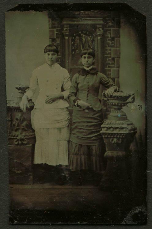 2 standing young women bangs studio tintype 1860s