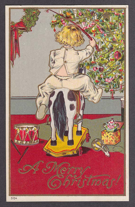 Boy riding toy horse next to tree embossed Christmas postcard 1910s