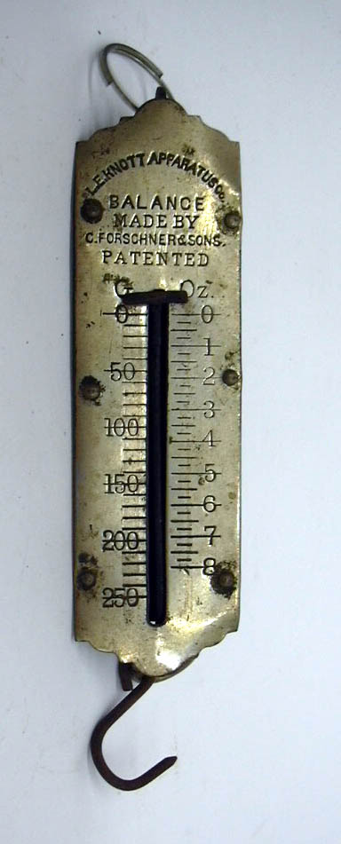 L E Knott Apparatus 8-ounce metal scale balance Made by C Forschner & Sons